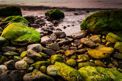 Mossy Rocks On Shoreline. Highly detailed mossy rocks on shoreline and soft sea waves in the sunset time on the Marmara region of the country Turkey Stock Photo