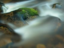 Mossy stone in blurred blue waves of mountain stream. Cold water is running and turning between boulders and bubbles create tr Stock Photos
