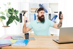 Most annoying thing about work in call center. Incoming call. Annoying client calling. Man bearded guy headphones office. Swing hammer on smartphone. Spoiled royalty free stock images