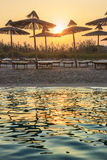 The most beautiful sandy beaches of Apulia.Torre Guaceto: umbrellas at sunset. It is Marine Protect Area and Nature Reserve with 8 Stock Photo