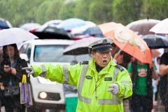 A policeman directing traffic in the rain. In most cities in China, traffic jams are becoming more and more serious with the popularity of domestic cars, which Royalty Free Stock Images