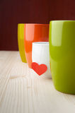Most delicious drink on valentine's day. Little white cup of hot drink among the large coloured cups Stock Images