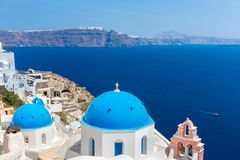 The most famous church on Santorini Island,Crete, Greece. Bell tower and cupolas of classical orthodox Greek church. With view of Mediterranean sea and Royalty Free Stock Photo