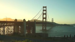 Golden Gate bridge sunset. The most famous landmark in San Francisco, the Golden Gate bridge at sunset. Silhouettes of tourists taking a tour stock video