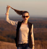 Fashionable,glamorous model stand on hills and held ponytail.Attractive,beautiful girl with sunglasses look at sunset. Very very beautiful,pretty,adorable,nice stock image