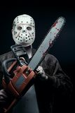 The most horrible nightmare. Maniac in mask holding bloody chainsaw stock photography