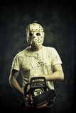 The most horrible nightmare. Scary mad maniac in mask with bloody chainsaw stock photo
