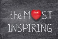 Most inspiring heart. The most inspiring phrase handwritten on chalkboard with red heart symbol instead of O stock photography