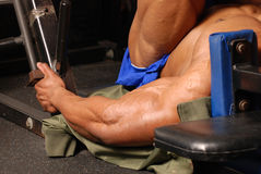 Most muscular. Tan male on leg press machine blue shorts side view powerful arms Royalty Free Stock Photo