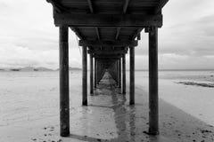 Most nad morzem podczas odpływu przypływu w czarny i biały Zdjęcia Stock