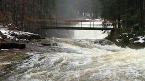 most nad wodą skołataną Ogromny strumień gnanie woda gromadzi pod małym footbridge Strach powodzie