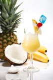 Most popular cocktails series. Pina Colada cocktails surrounded by tropical fruits. Rum, pineapple juice, coconut cream garnished with slice of pineapple royalty free stock image
