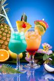 Most popular cocktails series - Mai Tai and Blue H. Mai Tai and Blue Hawaiian cocktails surrounded by tropical fruits. Most popular cocktails series Stock Image