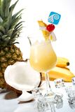 Most popular cocktails series - Pina Colada. Pina Colada cocktails surrounded by tropical fruits. Rum, pineapple juice, coconut cream  garnished with slice of Royalty Free Stock Photography