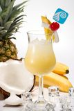 Most popular cocktails series - Pina Colada. Pina Colada cocktails surrounded by tropical fruits. Rum, pineapple juice, coconut cream garnished with slice of royalty free stock photo