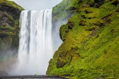 The most popular waterfall in Iceland - Skogafoss. Water rushes down with a crash, forming a cloud of mist. Picturesque huge royalty free stock photo