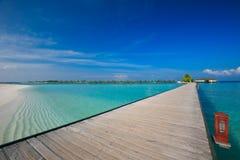 Most prowadzi overwater bungalow w błękitnej lagunie wokoło tropikalnej wyspy w Maldives Obrazy Stock