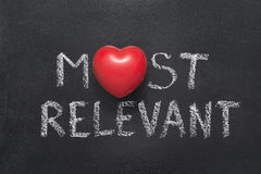 Most relevant heart. Most relevant phrase handwritten on blackboard with heart symbol instead of O Stock Photos