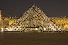 The Louvre of Paris by night. The most visited museum in the world, Louvre in Paris, France magnificent illuminated at twilight, as seen from the Denon Wing. Its stock images