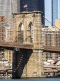 Mosta Brooklyńskiego wierza z usa flaga, Manhattan budynków tło wcześnie w ranku z niebieskiego nieba i słońca połyskiem Obrazy Stock