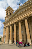Churches of Malta - Mosta Rotunda. Mosta, Malta - June 30, 2014: A group of tourist in front of six-columned portico of the monumental church of St Mary Royalty Free Stock Photo