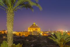 Mosta, Malta - The Mosta Dome or The Church of the Assumption of. Our Lady, commonly known as the Rotunda of Mosta with palm tree by night Royalty Free Stock Image
