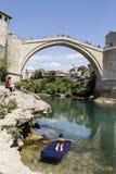 Mostar, Bosnië en Herzegowina, 15 Juli 2017: De jongen ligt op een luchtmatras voor de historische boogbrug Stock Foto's