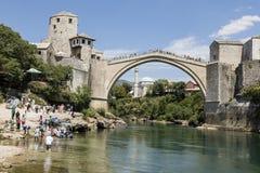 Mostar, Bosnië en Herzegowina, 15 Juli 2017: De toeristen genieten van de mening van de historische boogbrug over de neretvarivie Stock Afbeeldingen