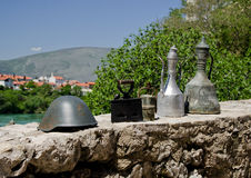 Mostar, Bosnia. Old brass jugs, iron and military helmet on marketplace in Bosnia Royalty Free Stock Photography