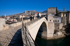 MOSTAR, BOSNIA AND HERZEGOVINA: Tourists walk down on the famous Old Bridge  Royalty Free Stock Photo
