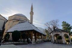 MOSTAR BOSNIEN OCH HERCEGOVINA JANUARI 26, 2018: Mehmet Pasha Mosque panorama och springbrunnGazebo i det Mostar centret Arkivfoto