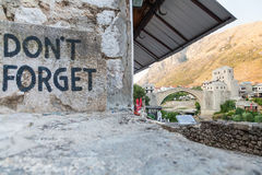 Mostar bridge and Don't Forget sign. MOSTAR, BOSNIA - AUGUST 10: View of Don't Forget sign and old bridge on August 10, 2012 in Mostar, Bosnia. The sign reminds Royalty Free Stock Photo