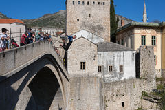 The Mostar Bridge. A young man dives from the Old Bridge to the river on April 15, 2015 in Mostar, Bosnia and Herzegovina. Stari Most diving is a very old Stock Photos