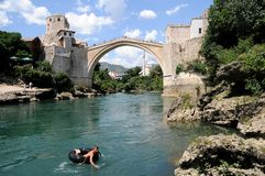 Mostar - the Old Bridge (Stari Most) with a boy. Photo of the old turkish bridge in Mostar connecting the Muslim (bosnian) side to the catholics (croats) - it Stock Photos
