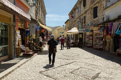 Mostar. A Street. MOSTAR, BOSNIA AND HERZEGOVINA - MAY 18, 2013: A tourist walks along a street full of shops, in the historic center of Mostar in Bosnia and Royalty Free Stock Photo