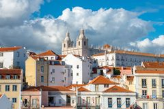 Colorful historic buildings and red tile roofs under a sky with dramatic clouds in Lisbon, Portugal stock photos