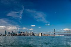 Blue skies fill the picture of the San Francisco skyline on the left and the bay bridge on the right with the moon in the. Mostly blue skies fill the picture of stock photography