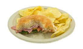 Mostly eaten salami sub sandwich on plate with chips Royalty Free Stock Photos