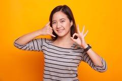 Mostra asiática nova da mulher com gesto do telefone e sinal APROVADO Imagens de Stock