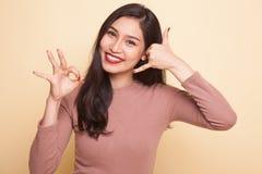 Mostra asiática nova da mulher com gesto do telefone e sinal APROVADO Fotos de Stock Royalty Free