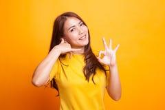 Mostra asiática nova da mulher com gesto do telefone e sinal APROVADO Fotografia de Stock