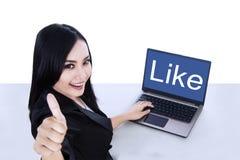 A mostra atrativa da mulher de negócios gosta e os polegares acima no portátil Fotos de Stock