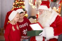 Mostra autentica di Santa presente ai bambini nella sala immagine stock