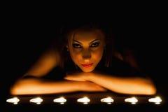Mostra da baixa luz do artista de uma menina bonita na vela imagens de stock