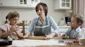 Mostra da mamã como à massa dos rolos para cookies na tabela na cozinha com as crianças video estoque