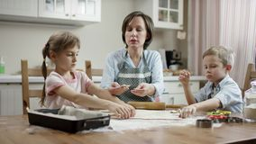 Mostra da mamã como aos biscoitos da disposição na maneira direita com foco na família filme