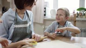 A mostra da mamã como fazer biscoitos na maneira direita e ajudar seu filho e aprovam-na video estoque