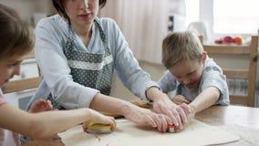 Mostra da mamã como fazer biscoitos na maneira direita e ajudar seu filho video estoque