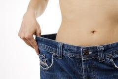 Mostra della donna quanto peso ha perso Fotografia Stock
