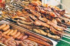 Mostra do alimento da rua com salsichas, salsichas e no espeto imagem de stock